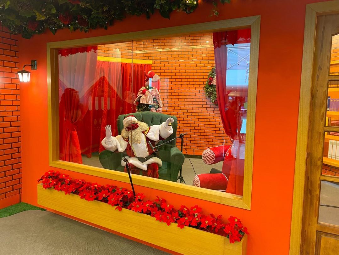 decoração natalina com cabine laranja e amarelo com cenário de natal e papai noel dentro
