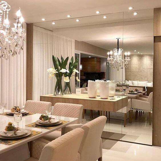 Sala com parede inteira espelhada, mesa de jantar branca com cadeiras estofada branca, lustre de cristal e piso porcelanato branco