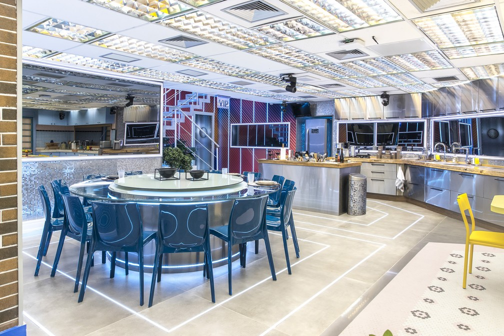 Cozinha vip possui ares industriais, que é possível identificar na marcenaria e revestimentos metalizados, piso no cimento queimado e a presença de detalhes com led, mesa redonda metalizada com cadeiras azuis.