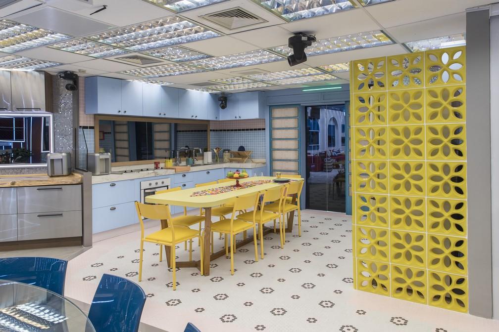 Cozinha com cobogó amarelo, armários azuis, revestimentos retrôs e mesa retangular amarela de 8 lugares.