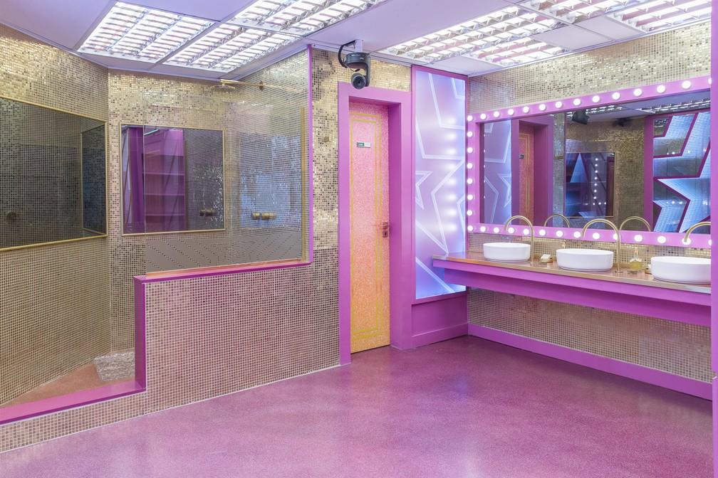 Banheiro em formato de camarim com em tom de cor neutra e rosa, com espelhos quadrados e retangular com luz de led.