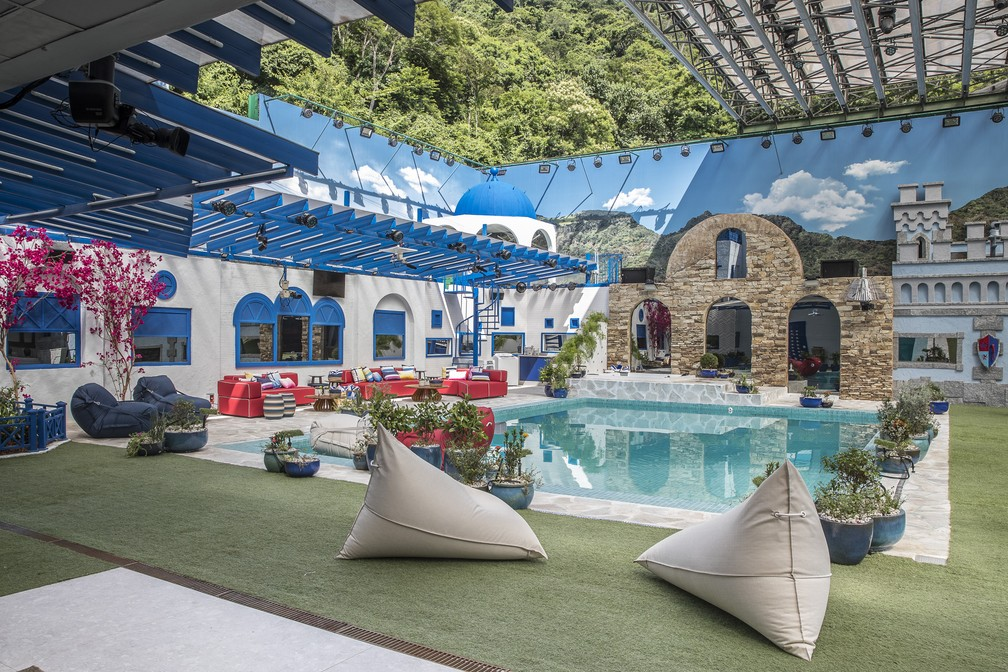 Área externa da casa com janelas arqueadas e pergolados com predominância nas cores azul e branca que transporta todos diretamente para a Grécia, piscina retangular, completando com um castelo medieval onde ficará o quarto do líder.