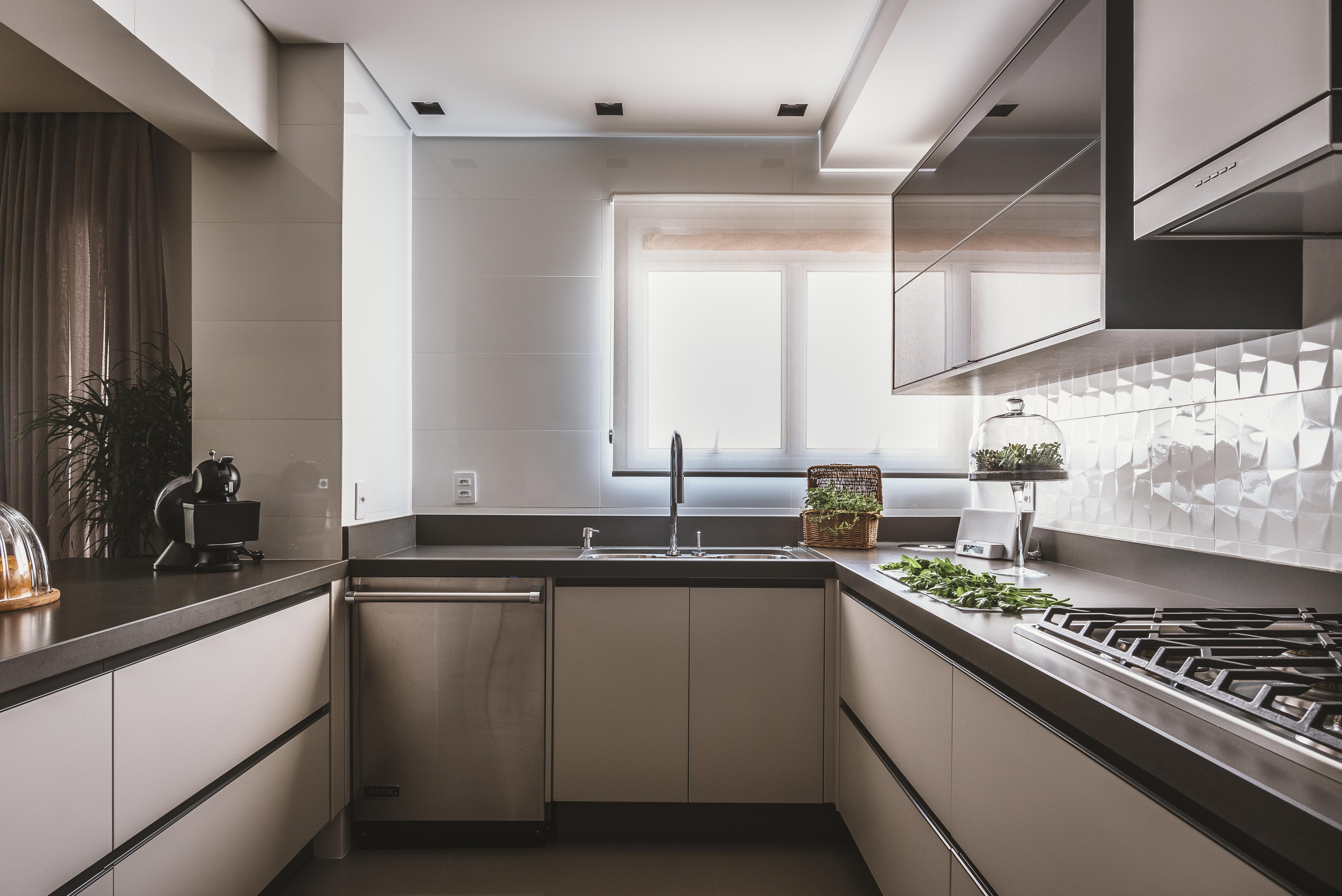 Cozinha com revestimento 3D na parede de porcelanato com efeito polido contrastando com a pedra fosca, armários em tom neutro e bancas cinza escuro e piso neutro.