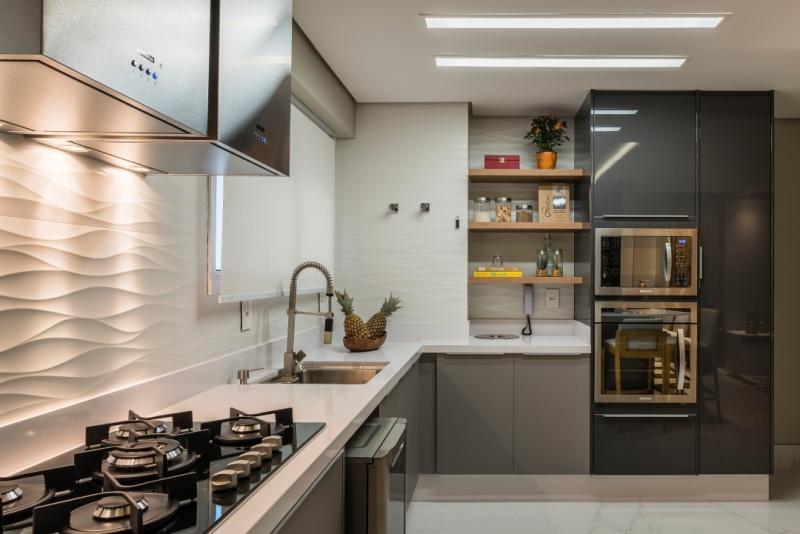 Cozinha com revestimento 3D nas paredes com efeito onda, armários cinza e bancadas brancas.
