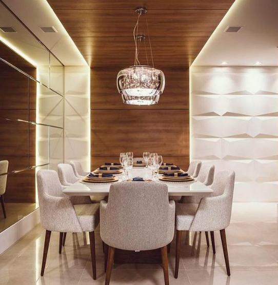 Sala de jantar com revestimento 3D cimentício com detalhe de madeira no canto cobrindo até o teto. Mesa branca de jantar com 8 cadeiras estofadas, espelho na parede inteira lateral, luminária pendente transparente e piso em tom neutro.