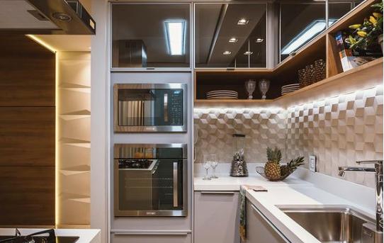 Cozinha com revestimento 3D de porcelanato, bancada e armários inferiores branco e superiores madeirado e espelhado,