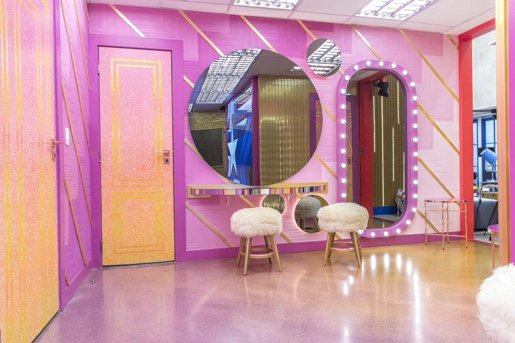 Área de circulação do banheiro com espelhos em formatos diferentes, bancos com estofado de pelúcia.