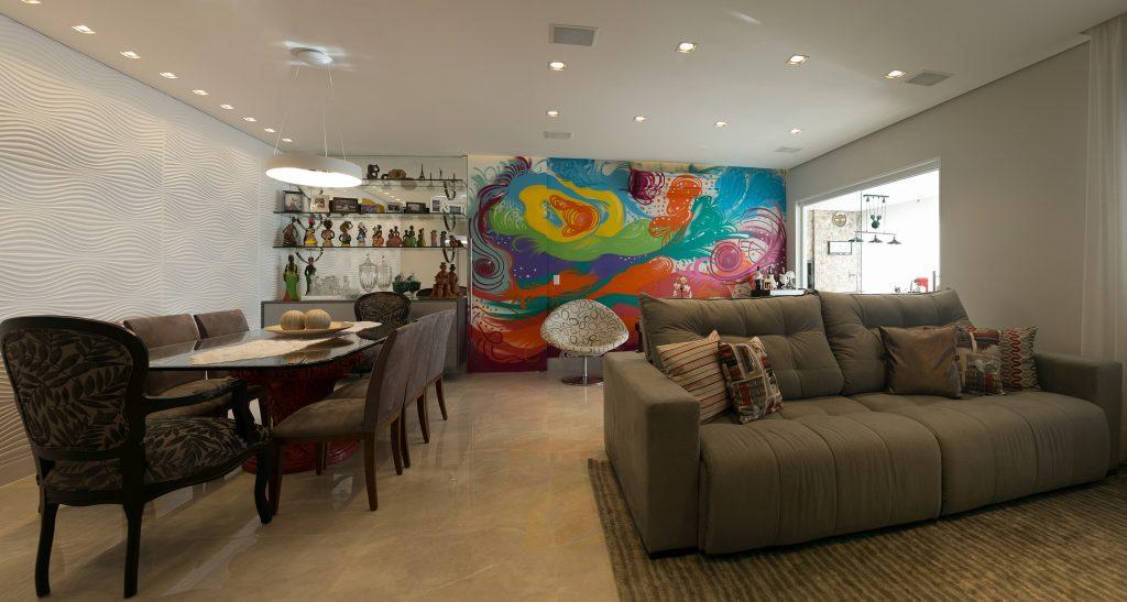 PB Arquitetura, - Sala de estar com graffiti colorido do artista visual Fernando Reche na parede de fundo da sala, piso porcelanato em tom neutro, sofá bege com tapete na mesma tonalidade, sala integrado