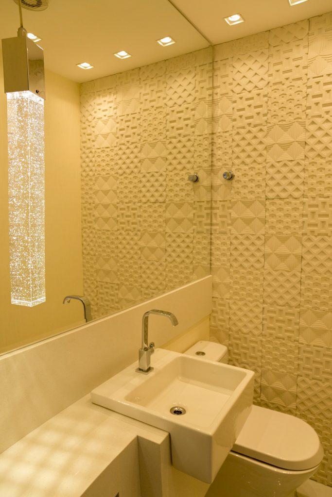 Lavabo com revestimento branco 3D na parede, bancada e cuba branca, luminária pendente comprida e espelho retangular grande.