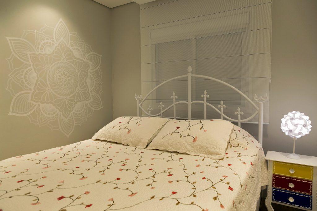 Quarto com cama de casal com cabeceira de ferro branco, paredes em tom cinza claro, parede lateral com desenho de mandala, cortina com persiana na parede de fundo e criado mudo branco com gavetas coloridas