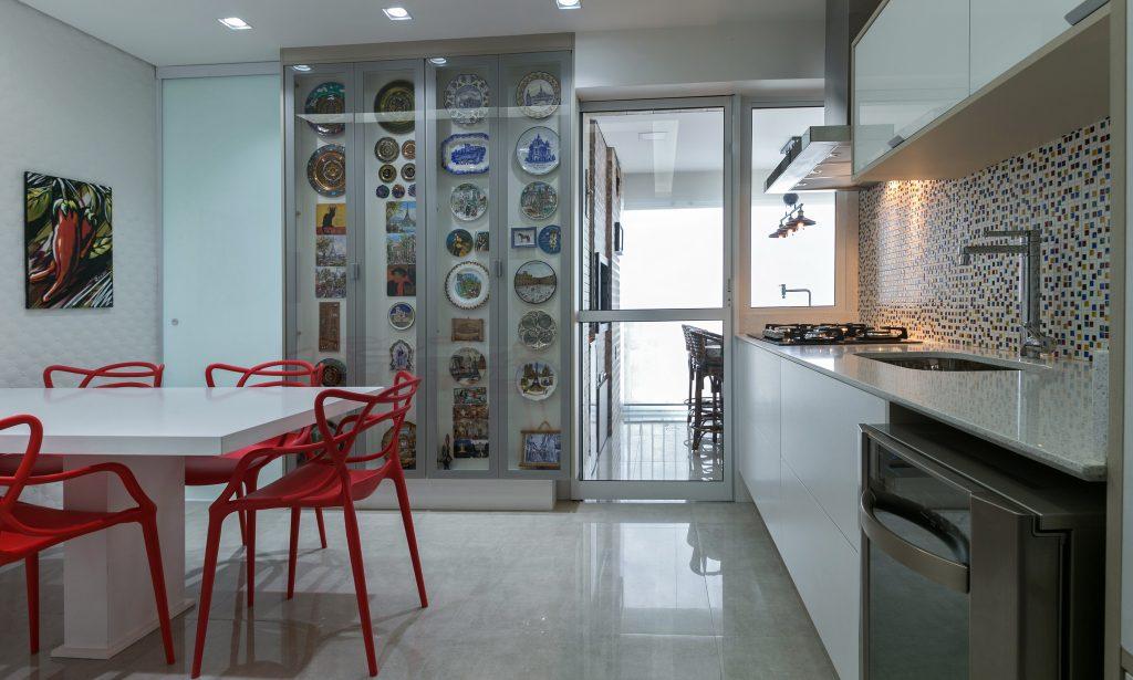 Cozinha com piso porcelanato em tom claro, armários brancos, pastilha preta e branca na parede da pia, mesa branca com cadeiras vermelhas e painel em vidro com coleção de pratos do casal