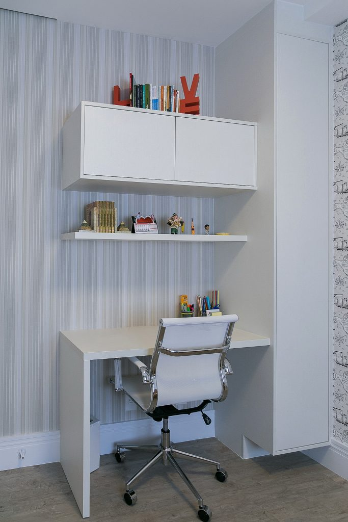 Cantinho de Home office, estudos com piso de madeira cinza, móvel planejado com escrivaninha, armários e prateleiras branco e papel de parede listrado em tons claros.