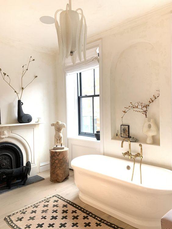 Banheiro com paredes brancas, piso de madeira clara, tapete pra banheiro, vaso decorativos pretos,  de pedras e brancos.