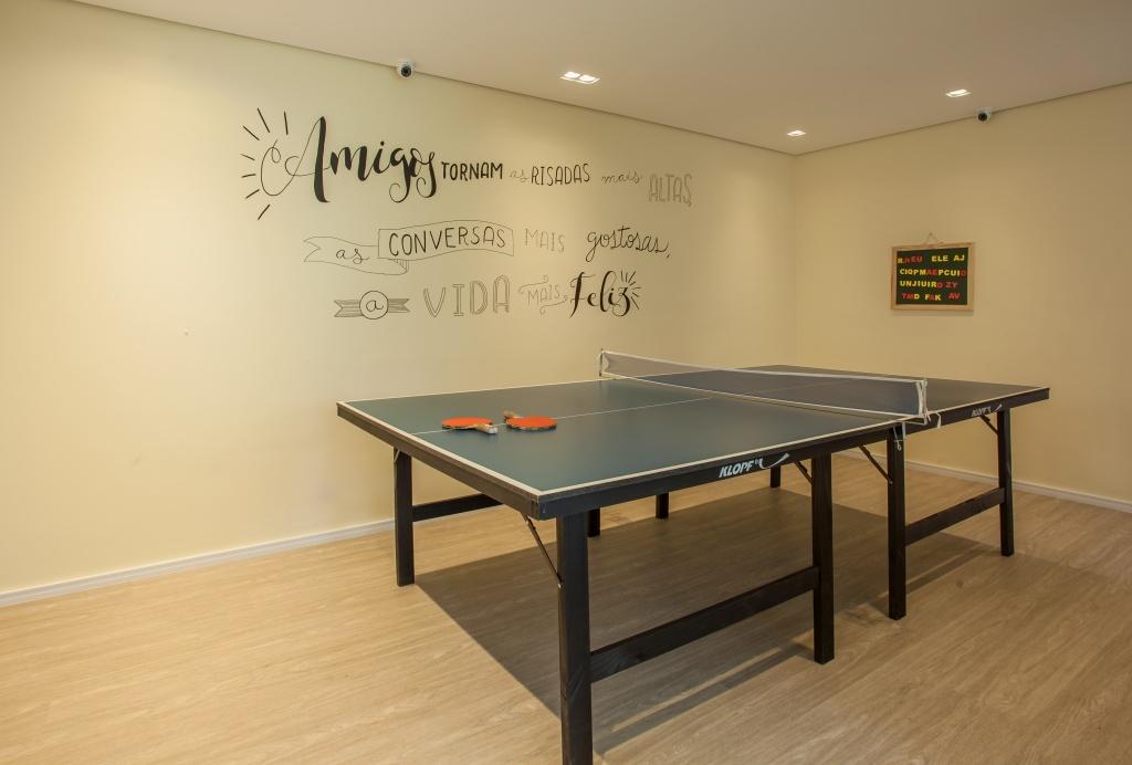 Sala de jogos com mesa de pebolim, piso de madeira, paredes em tons claros com adesivos de frases.
