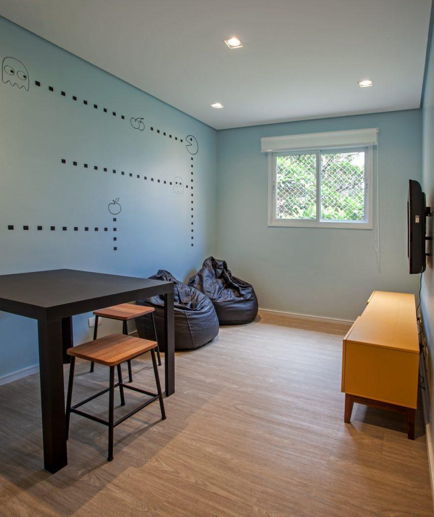 salão de jogos com piso de madeira, paredes azul com desenho de games, TV, rack amarela, puff e mesa preta e banquetas de madeira