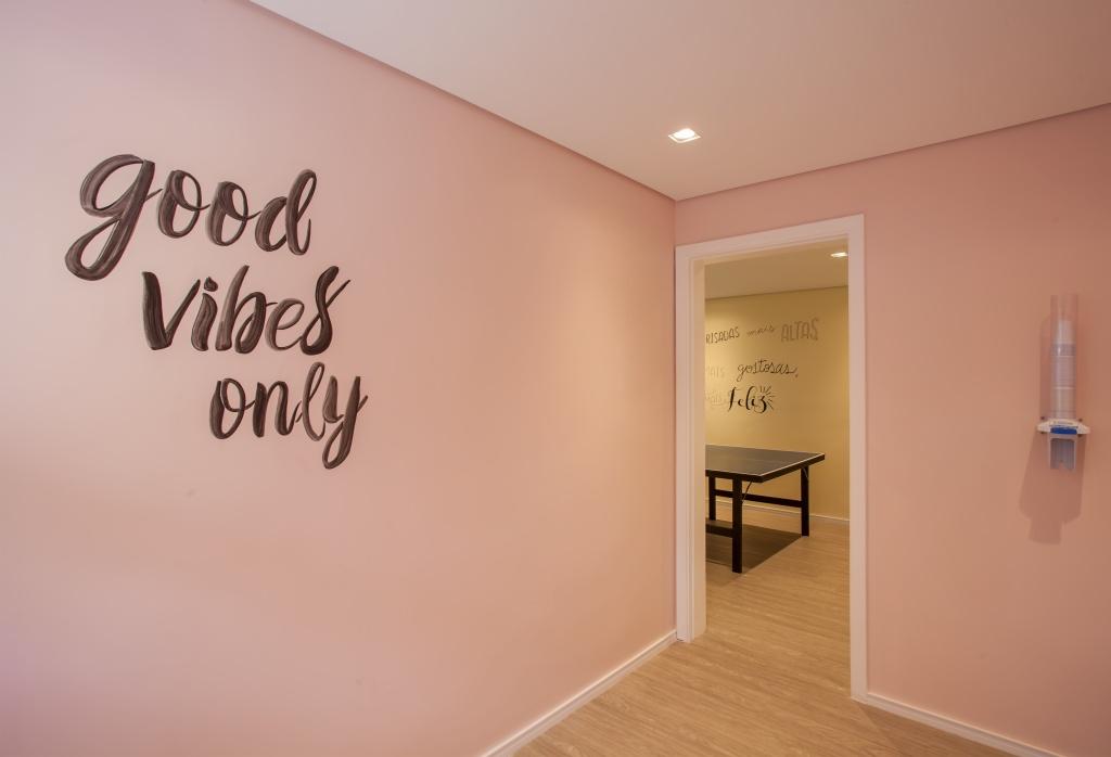 """Hall de entrada da sala com  piso de madeira, paredes rosa com adesivo preto com frase """"good vibes only"""""""