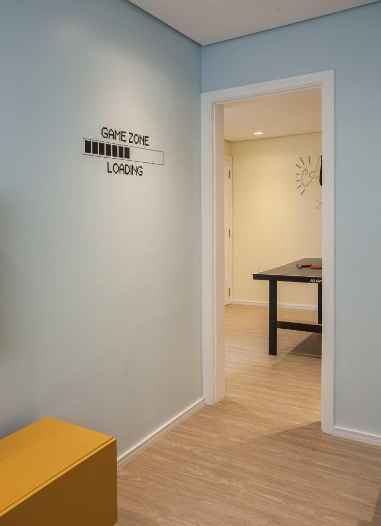 Hall de entrada de salão de jogos com piso de madeira, paredes azul com adesivos.
