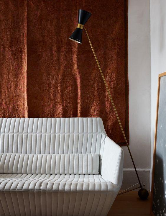 Sala de estar com sofá branco e tapete na parede