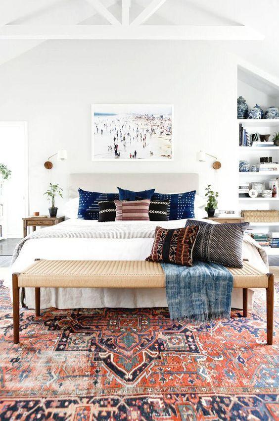Quarto com tapete persa colorido, paredes e móveis brancos, banco largo no pé da cama de palha.
