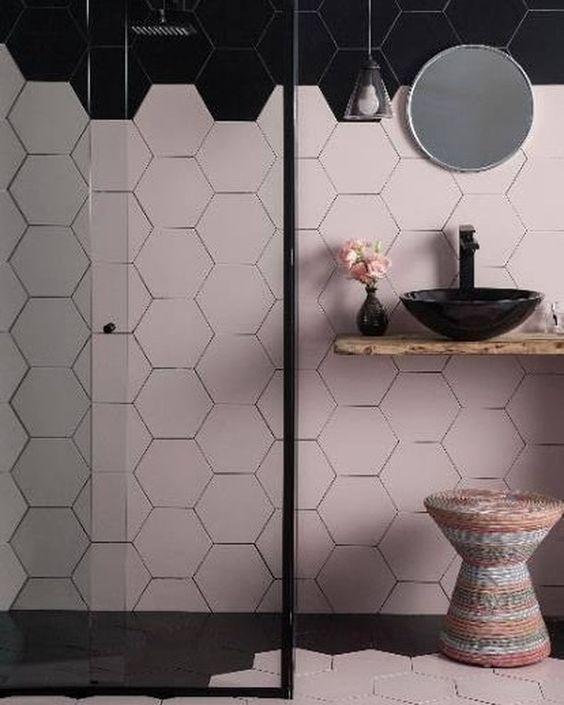 Banheiro com revestimento hexagonal rosa e preto na parede e piso, cuba preta, banco colorido de palha e box de vidro com moldura preta