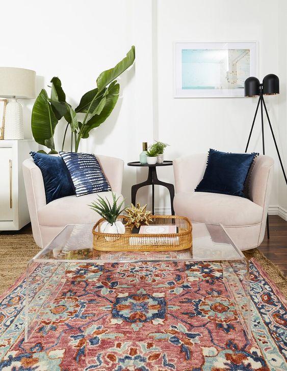 Sala de estar contemporânea com poltronas branca e almofadas azul, tapete no chão de madeira, prede brancas, abajur branco e luminárias pretas