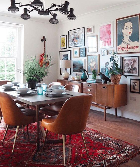 Sala de jantar com tapete colorido, mesa cinza retangular com cadeiras amadeiradas, móvel d emadeira com abajur e objetos decorativas e parede com muitos quadros.
