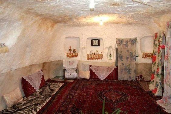 Casa persa tradicional com tapetes pelo chão, almofadas e cortina reproduzindo portas.