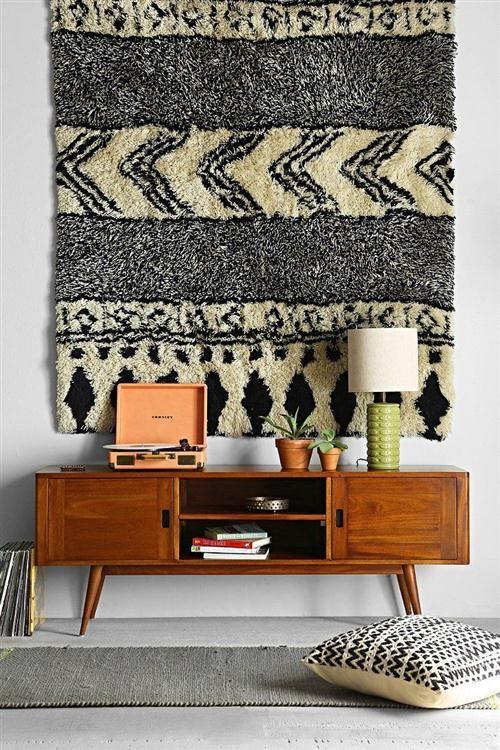 Hall com móvel rack de madeira com abajur e livros, tapete na parede, passadeira no chão e almofada