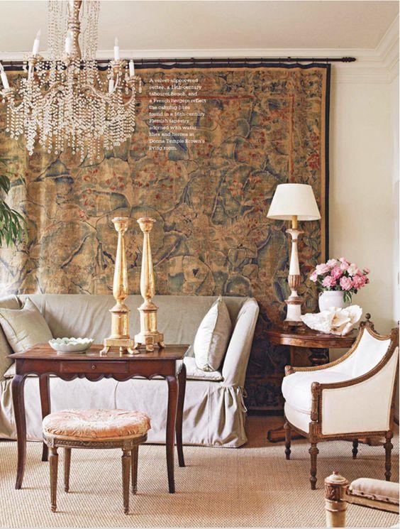 Sala de estar com tapeçaria na parede, sofá com capa em tom neutro, poltrona branca, mesinha de centro de madeira, banco redondo estofado, abajur branco e lustre de cristal.