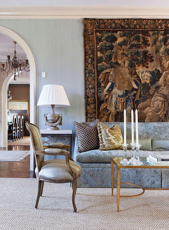 Sala de estar com tapeçaria na parede, sofá azul claro, poltronas prata, mesinha de centro de vidro com velas, abajur branco, parede azul claro e tapete em tom neutro no chão de madeira.