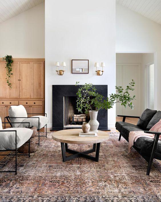 Sala contemporânea com paredes brancas, tapete grande na sala, mesinha de centro redonda de madeira, sofá preto, poltronas com estofado branco, armário amadeirado e lareira com borda de porcelanato preto.