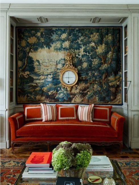 Sala intima com tapeçaria na parede, relógio grande dourado, sofá laranja com almofadas, tapete no chão, mesinha de centro de vidro com livros e vaso de planta.