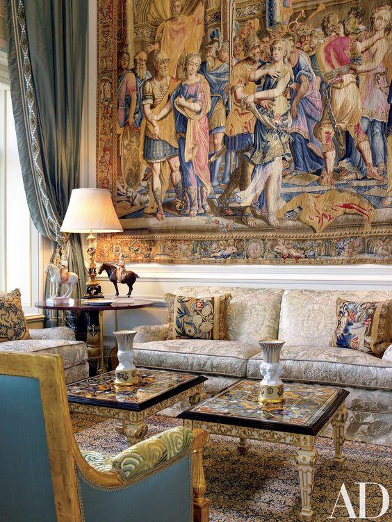 Sala com tapete na parede, Interior de Juan Pablo Molyneux, sofá em tom neutro com almofadas coloridas, mesinhas de centro personalizadas, poltrona azul e tapete no chão.