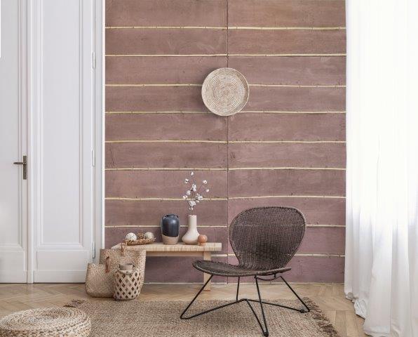 tendências de revestimentos e decoração para 2021 - ambiente com revestimento na parede inspirado no pau a pique, piso de madeira, cadeira de palha marrom, e banquetinha de madeira com objetos decorativos