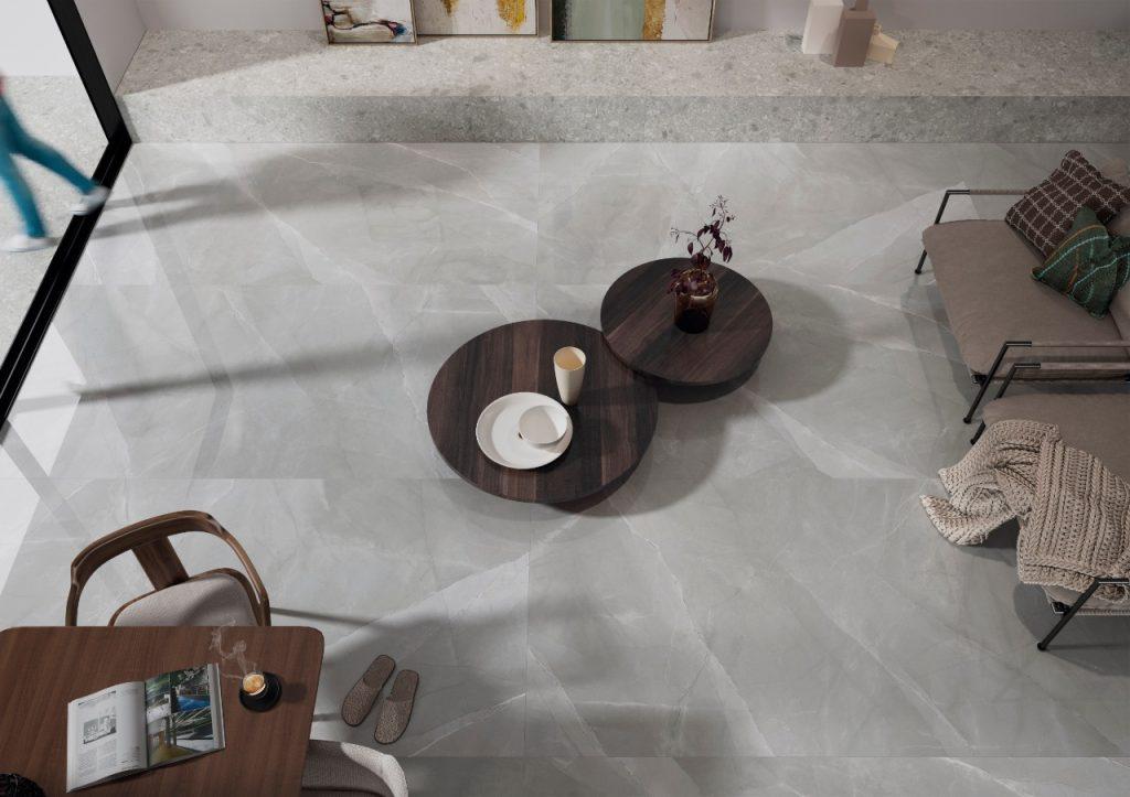 ambiente com porcelanato em grande formato marmorizado em tons cinza, mesinhas de centro redonda de madeira, duas poltronas com almofadas, mesa com cadeira.