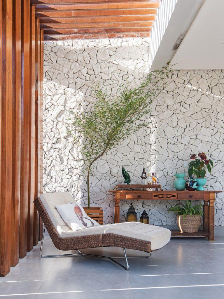 tendências de revestimentos e decoração para 2021 - área externa com parede revestida de pedras naturais, piso porcelanato cinza, móvel de madeira com vasos e objetos decorativos, espreguiçadeira e árvore pequena.