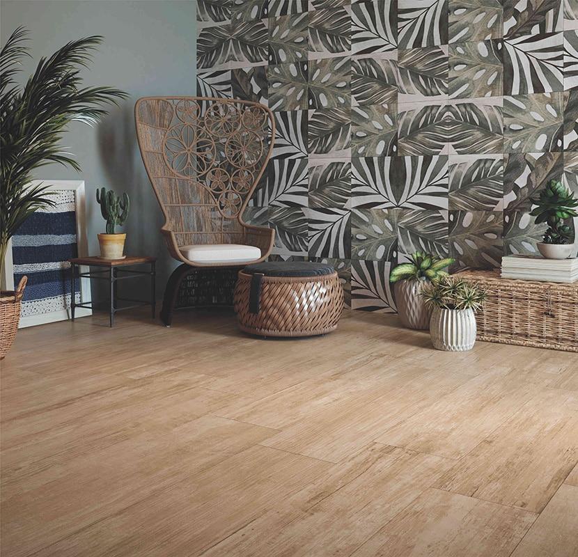 tendências de revestimentos e decoração para 2021 - ambiente com papel de parede de folhas verdes, piso de madeira, cadeira de madeira, cestas e baús de palhas e vasos de plantas decorativos.
