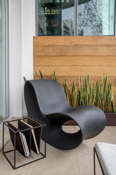 Área externa com parede revestida de madeira de demolição, beiral de plantas, cadeira preta com design moderno, porta revestidas preto e piso em tom neutro.