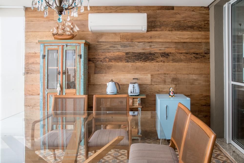 Varanda com parede principal revestida de madeira, cristaleira e criado mudo amadeirado com detalhes azuis, frigobar azul, mesa de vidro com cadeiras de madeira e piso de ladrilho hidráulico.