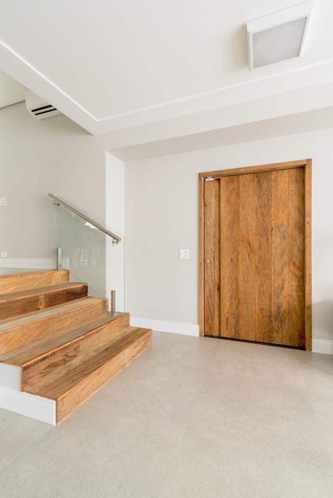 hall de entrada da casa com degraus e porta de madeira de demolição, piso porcelanato e paredes brancas.
