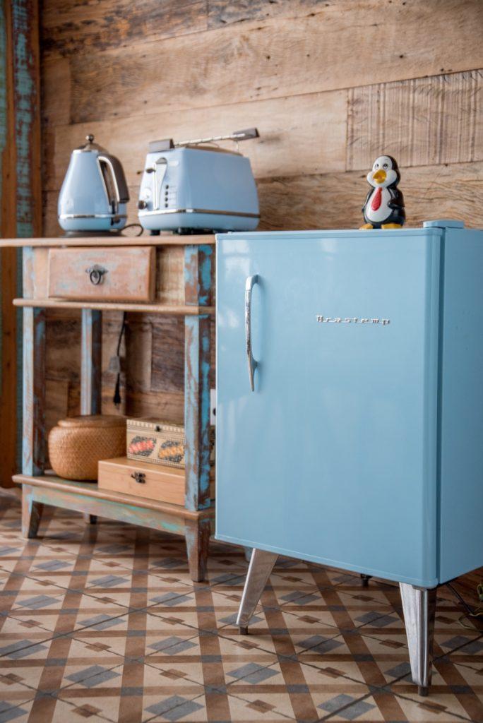frigobar azul, criado mudo rustico amadeirado com detalhes azul e piso de ladrilhos hidráulico.
