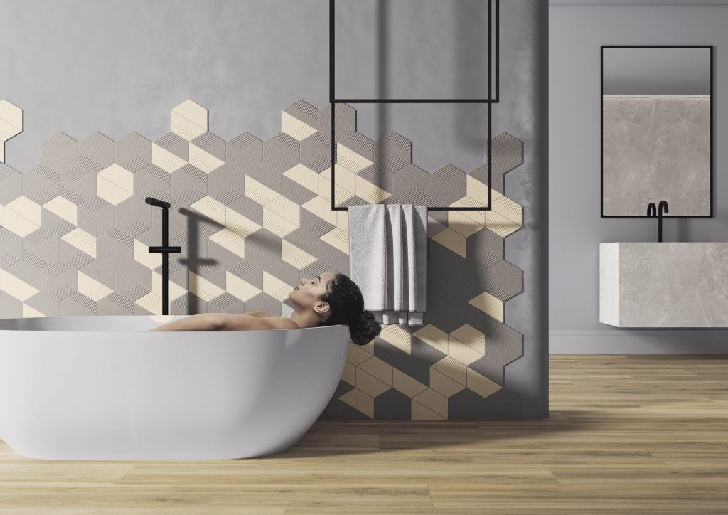 Banheiro com piso de madeira, paredes azul claro, cuba de cimento queimado, acima espelho retangular com moldura preta, parede da banheira com revestimento hexagonal.