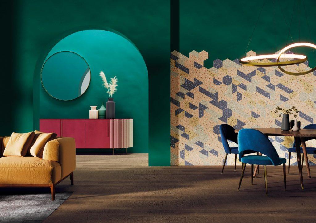 ambiente com paredes verdes, piso de madeira, parede com revestimento hexagonal de granilites, mesa redonda de madeira com cadeiras azuis e sofá amarelo.