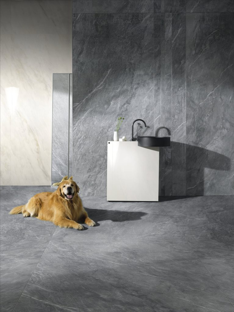 Ambiente com cuba preta, bancada branca, revestimento marmorizado cinza nas paredes e piso e um cachorro deitado