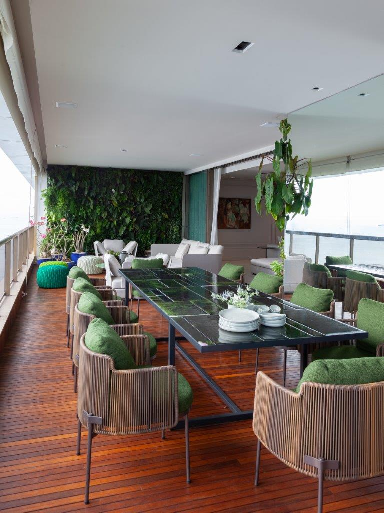 Sacada com mesa retangular grande verde e cadeiras amadeiradas com estofado verde, piso de madeira, no fundo jardim vertical com sofás branco e vasos de plantas decorativos.