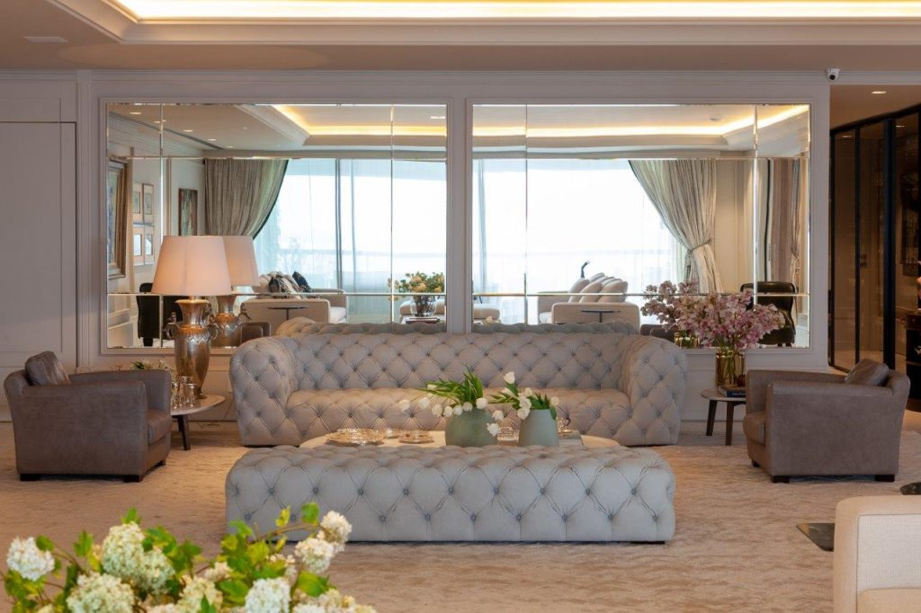 Sala com sofás cinza e branco capitone,  espelho e cristais pela sala, tapete em tom neutro e abajur branco