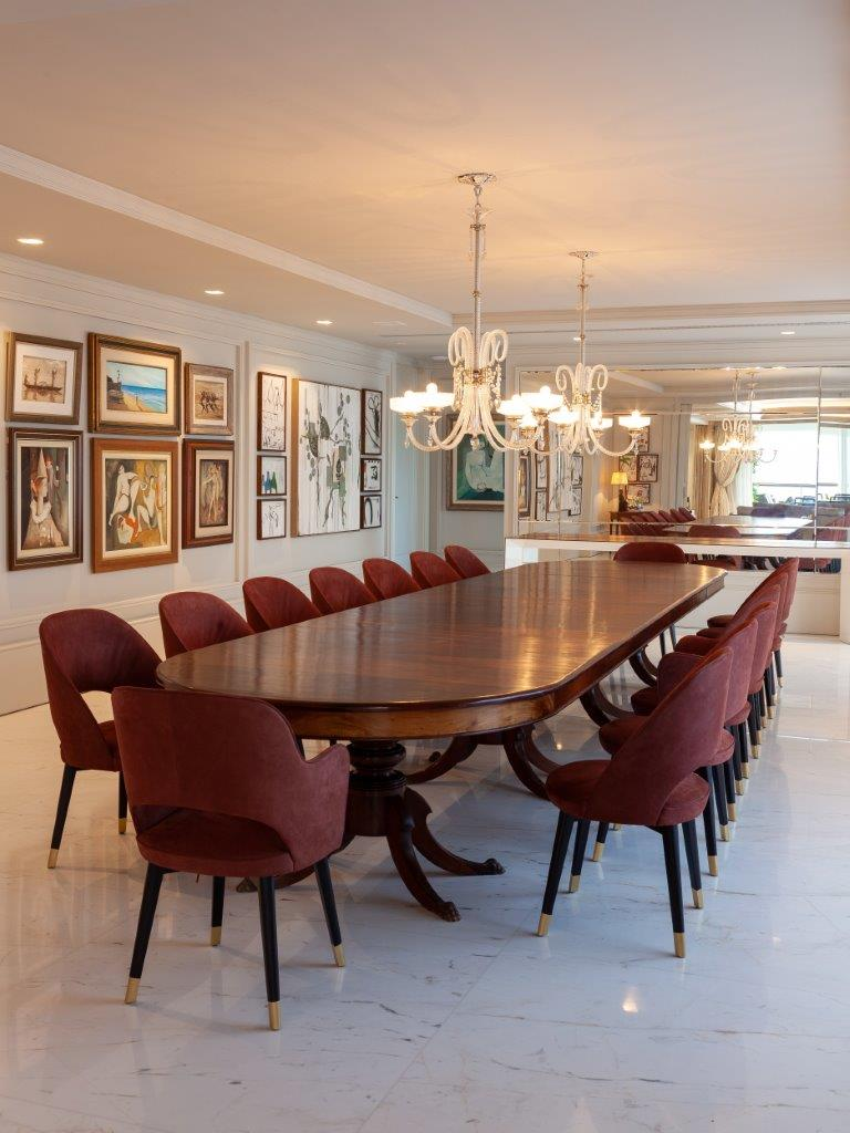 Sala de jantar com mesa grande de madeira com 16 cadeiras vinho, piso porcelanato branco, lustre branco, paredes brancas com diversos quadros decorativos e espelho
