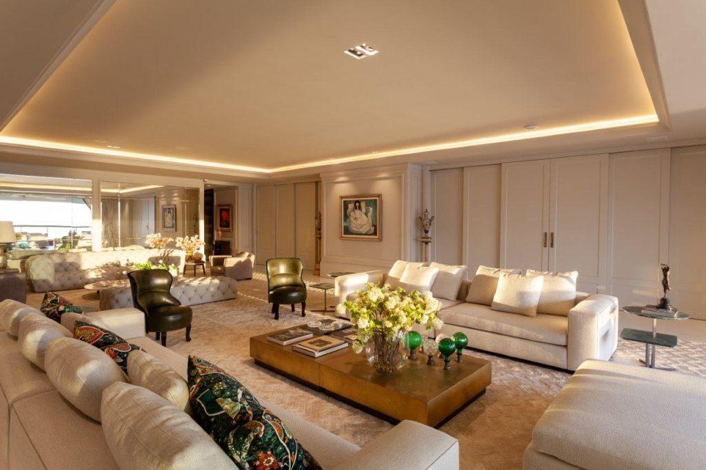 projeto do apartamento com décor clássico, sala de estar com sofás brancos, poltronas e mesinha de centro em bronze, paredes e portas brancas.