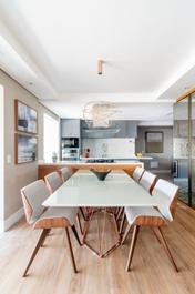 Mesa de jantar cumprida branca com 6 cadeiras brancas e estrutura de madeira
