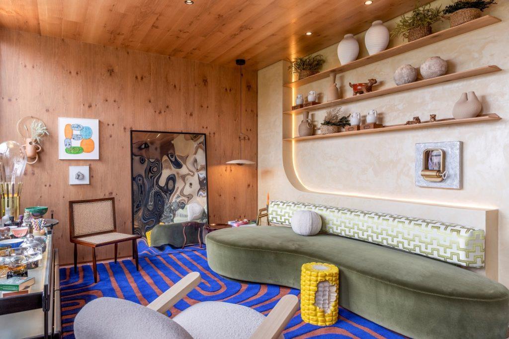 Living Galeria: Ambiente com revestimento de madeira na parede e teto, janela grande com detalhes na estrutura de ferro, tapete azul e marrom, piso de cerâmica, sofá verde, poltrona branca, mesinhas de centro laranjas e prateleiras com muitos objetos